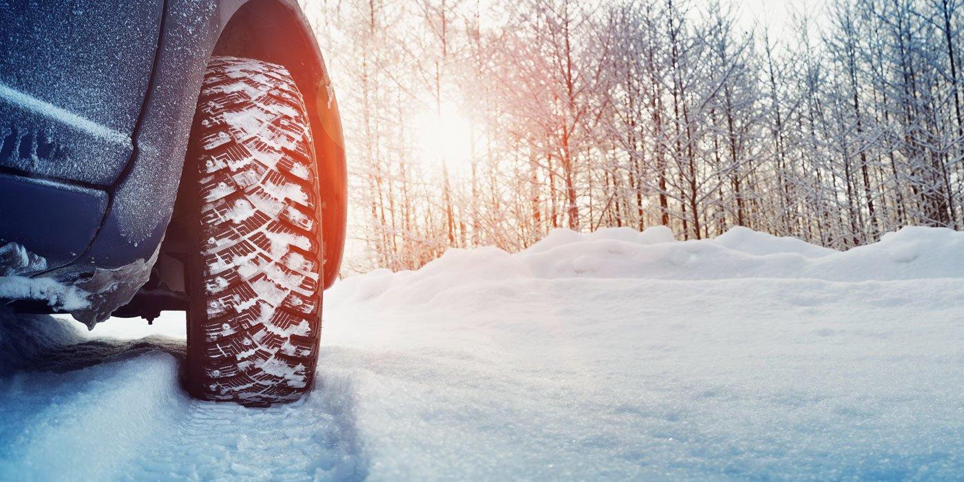 Ein Auto mit Winterreifen durchquert eine schneebedeckte Straße