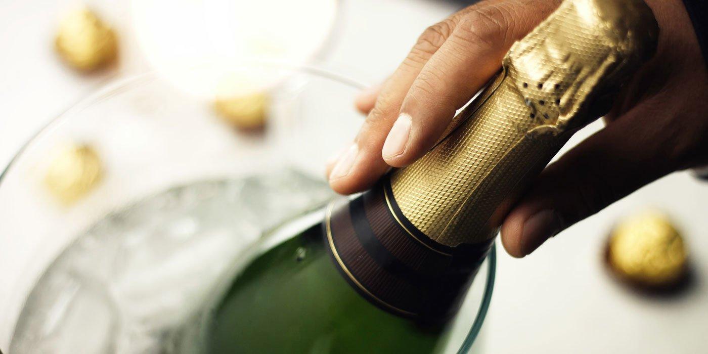 Eine Champagnerflasche mit sichtbarem Etikett liegt in einem Kühler