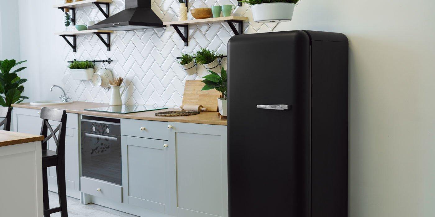 Schwarzer Retro-Kühlschrank steht in grau-weißer Küche mit schwarzen Elementen