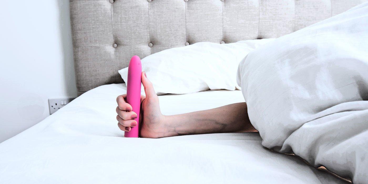 Eine Frau hand hält einem Dildo in der Hand. Die Frau selbst liegt unersichtlich im Bett unter der Bettdecke