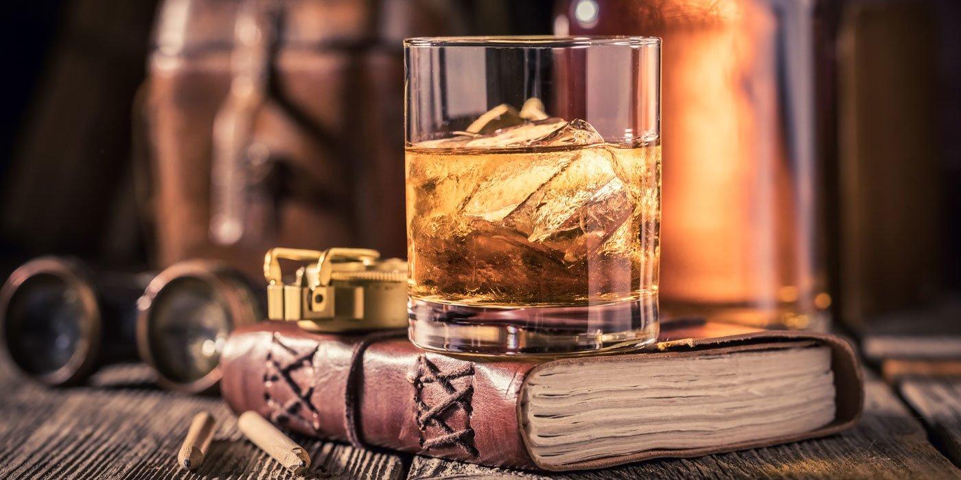 Ein Whiskyglas steht auf einem Buch, im Hintergrund ist eine Whiskyflasche