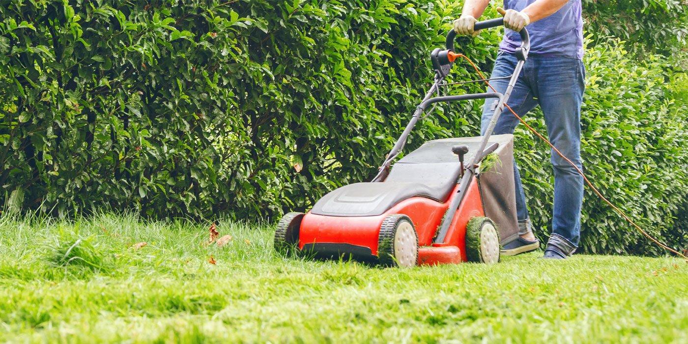 Ein Mann mäht den Rasen in seinem Garten