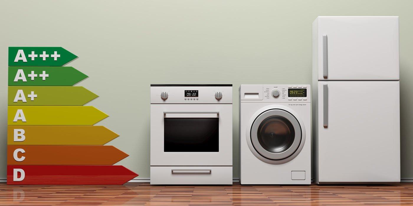Energielabel neben einem Backofen, einer Waschmaschine und einem Kühlschrank auf Parkettboden