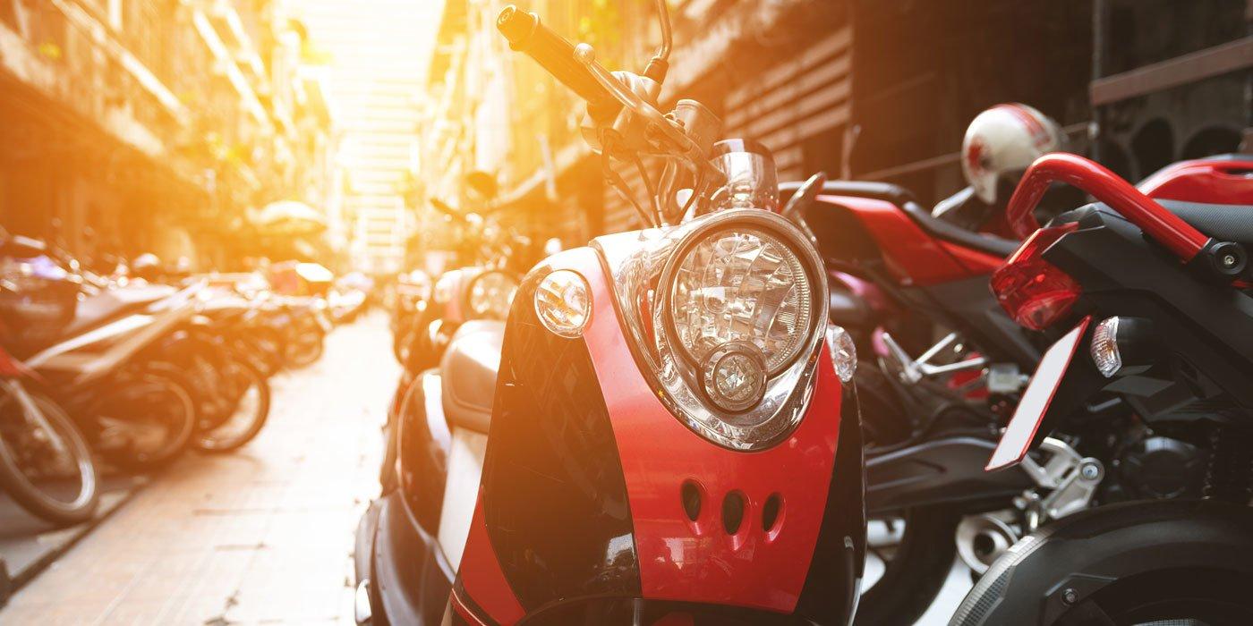 Frontansicht eines Motorrollers der auf einer Straße mit parkenden Motorrollern steht