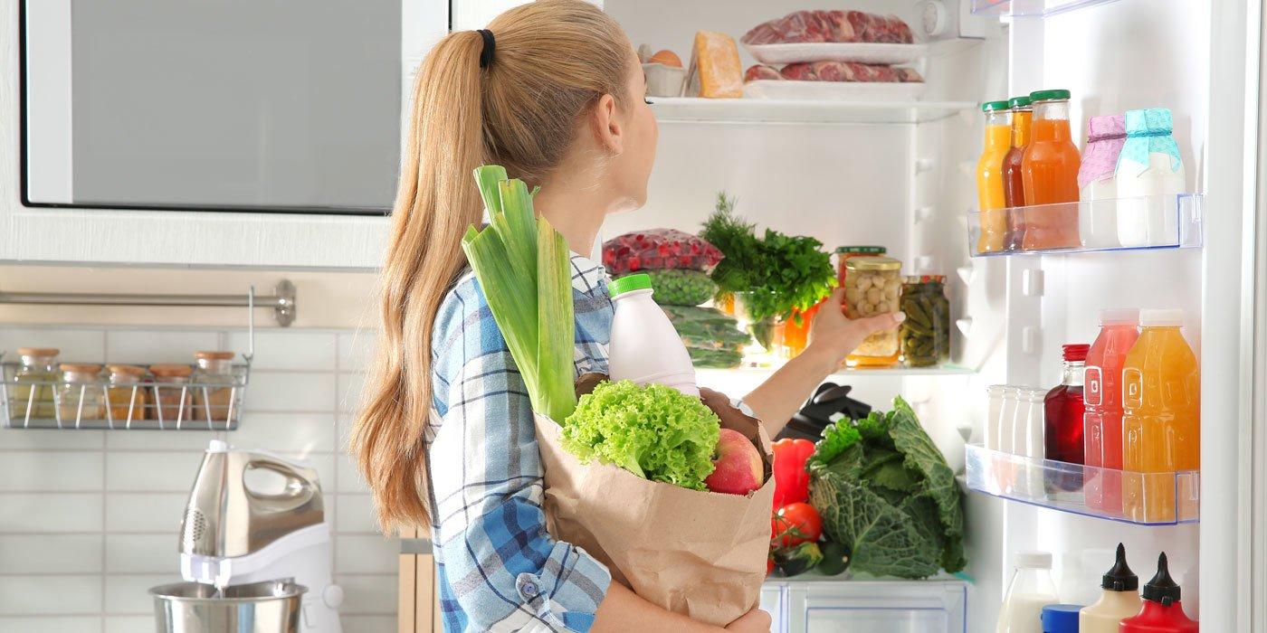 Frau räumt Einkäufe in den geöffneten Kühlschrank