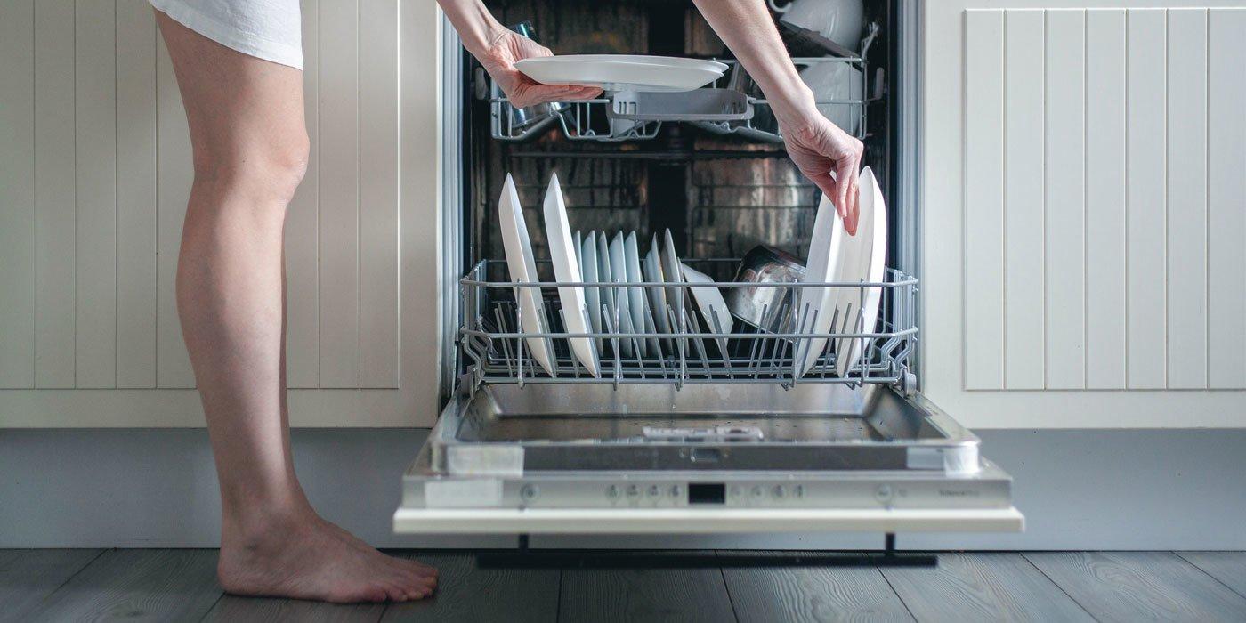 Eine Frau lädt dreckiges Geschirr in den Geschirrspüler ein