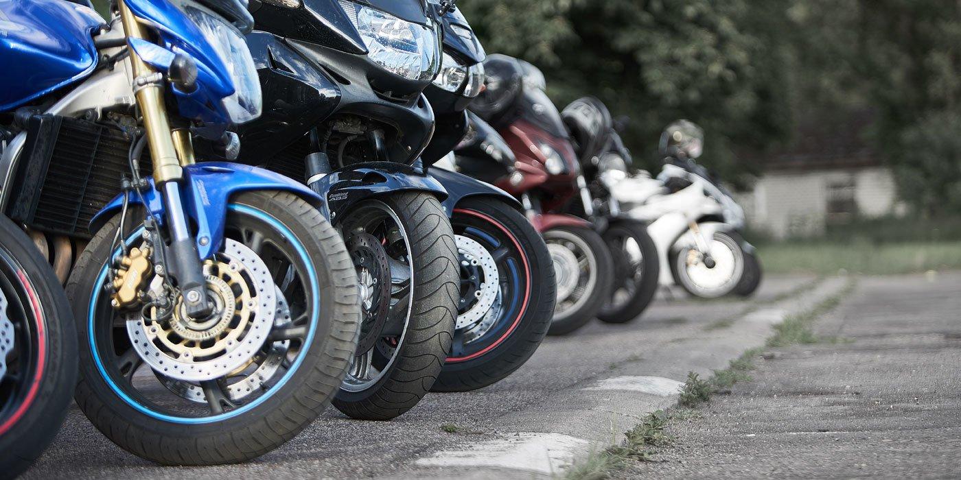 Mehrere Motorräder stehen auf einer asphaltierten Straße