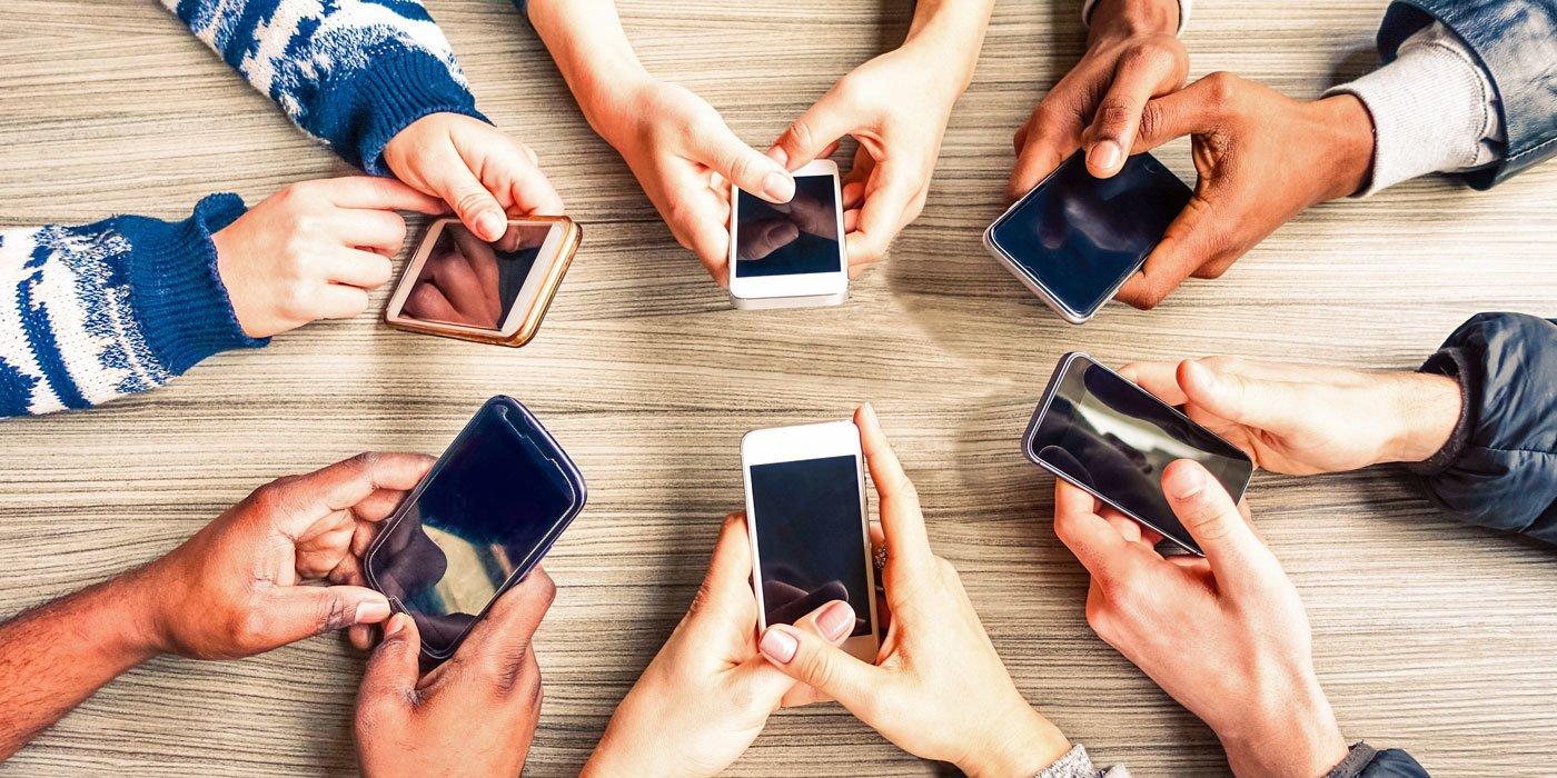 Hände verschiedener Hautfarben halten je ein Handy, kreisförmige Anordnung