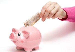 Person steckt 50-Euro-Schein in ein rosanes Sparschwein