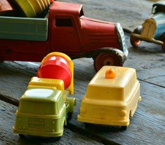 Mehrere Spielzeug-Fahrzeuge stehen auf einem Holzuntergrund