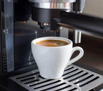 Mit Kaffee gefüllte, weiße Tasse unterhalb einer Kaffeemaschine