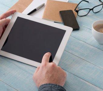 Mann möchte Tablet benutzen, aber der Akku ist leer. Das Display bleibt schwarz.