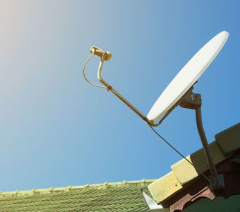 Satellitenschüssel auf Hausdach zeigt in den blauen Himmel