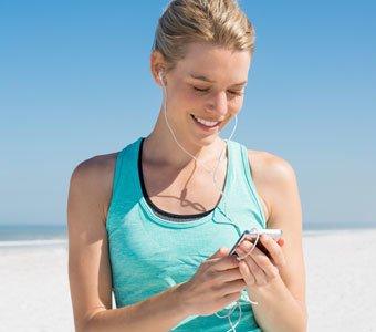 Frau steht am Strand und blickt freudig auf das Display ihres Audio-Players.