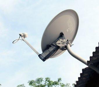 Satellitenschüssel ragt am Dach eines Hauses in den Himmel
