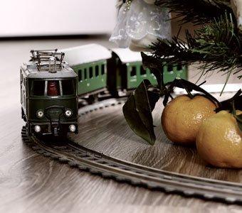 Grüne Modelleisenbahn fährt um einen angedeuteten Weihnachtsbaum