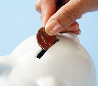 Person steckt Geldstück in den Schlitz einer Spardose