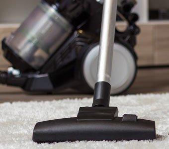Staubsauger mit Bodendüse auf weißem Teppich