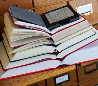Ein eBook Reader liegt an oberster Steller eines Stapels aufgeschlagener Bücher.