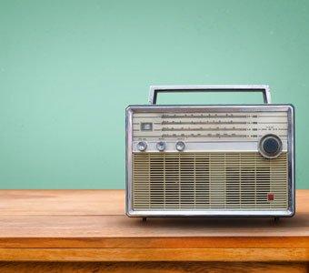 Graues Vintage-Radio steht auf hölzernem Untergrund.