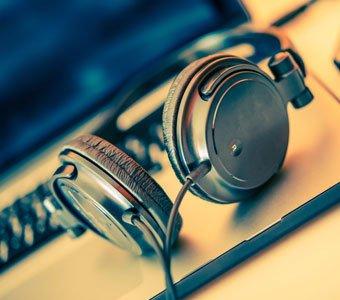 Kabel-Kopfhörer liegen auf dem Gehäuse eines geöffneten Notebooks.