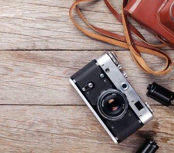 Klassische Analog-Kamera liegt auf einem Holzuntergrund neben einer Ledertasche
