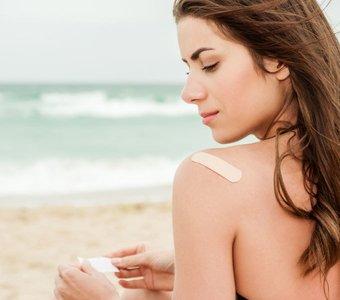 Junge Dame klebt ein Nikotinpflaster auf ihre Schulter.