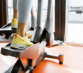 Nahaufnahme Beinbereich einer Frau beim Training mit dem Crosstrainer