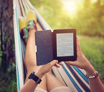 Junge Frau nutzt die Sonne und liest auf ihrem eReader in der Hängematte
