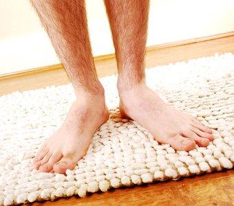 Beine eines Mannes, die auf einem weißen Badezimmerteppich stehen