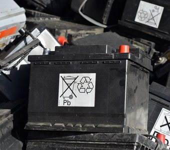 Eine Autobatterie liegt zusammen mit anderen Batterien auf einer Entsorgungsstation