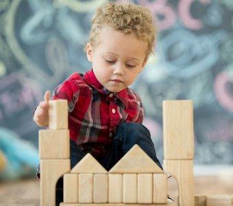 Kleiner Junge baut eine Burg aus Holzbausteinen