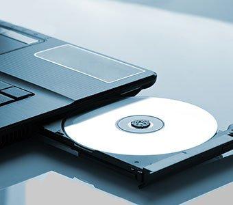 Geöffnetes Laufwerk eines Notebook mit eingelegter CD-ROM.