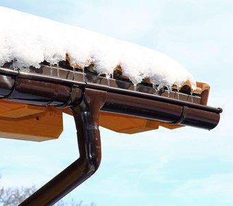 Ein schneebedecktes Schrägdach, von dem die Eiszapfen herunterhängen.