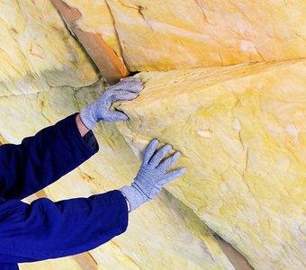 Handwerker beim Einlegen von Dämmungsmatten am Dach