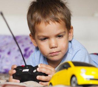 Jung lenkt mit der Steuerung ein RC-Modellauto