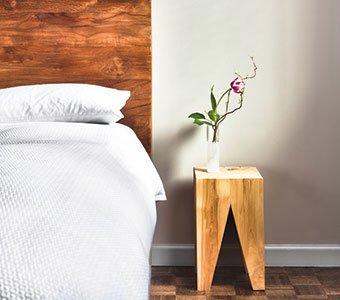 Aufnahme eines hölzernen Nachttisches neben einem Bett.