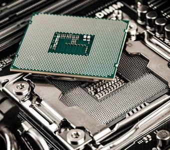 Ein Prozessor liegt auf dem CPU Sockel des Mainboards