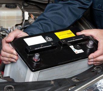 Eine Autobatterie wird vom Fachpersonal aus dem Motorraum entnommen