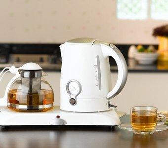 Wasserkocher und Teekanne auf einem Sockel, daneben eine Tasse Tee
