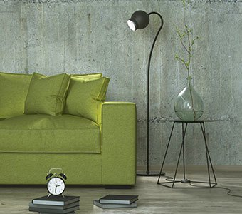 Totale einer Lampe, welche ein Sofa beleuchtet.