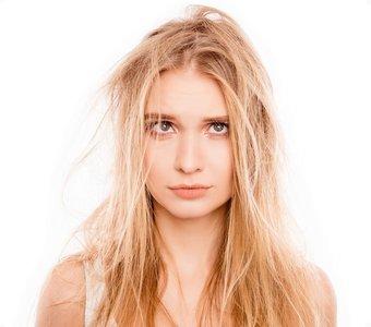Junge, blonde Frau ärgert sich über ihre kaputten Haare
