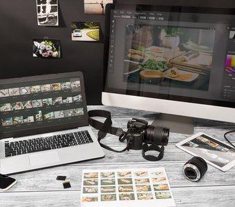 Schreibtisch mit PC, Laptop, Kamera und Bildern