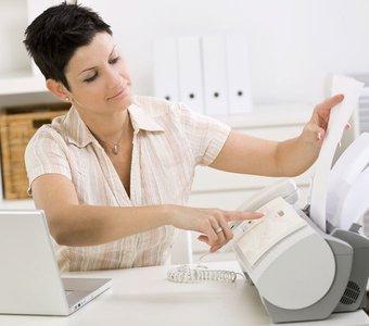 Eine Frau sitzt am Schreibtisch und legt ein Dokument in ein Faxgerät ein
