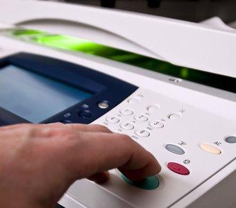 Eine Hand bedient die Tasten eines Multifunktionsdruckers, im Hintergrund leuchtet grünes Licht unter der Scannerklappe des Geräts