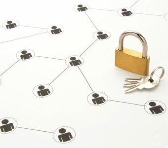 Personenicons sind in einer schwarz-weißenGrafik miteinander verbunden, daneben liegt ein Vorhängeschhloss und dessen Schlüssel