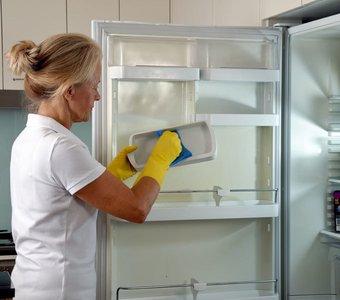Blonde Frau reinigt ihren Kühlschrank gründlich mit einem Schwamm