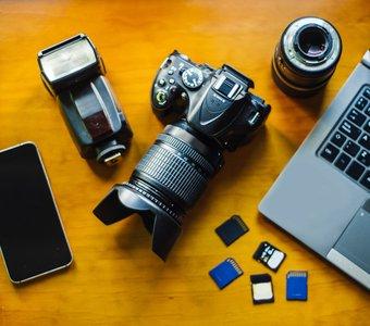 Objektiv, Speicherkarten, Kamera und Blitzlicht liegen auf einem Schreibtisch