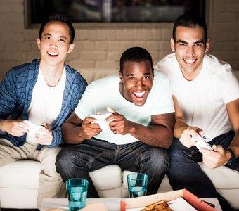 Junge Männer zocken zusammen auf der Couch