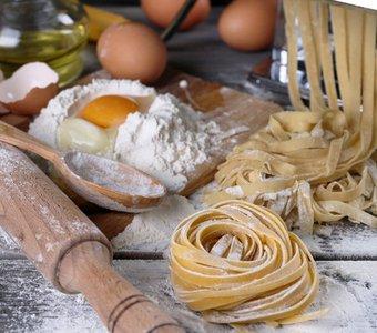 Nudelmaschine, aus der geschnittener Nudelteig kommt, davor Nester aus bereits fertig geschnittenen Pastastreifen